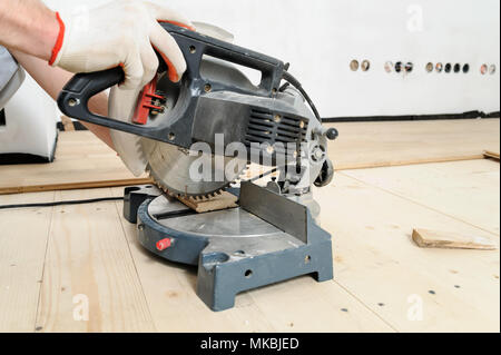 Worker cuts wooden floorboards using a circular saw. - Stock Photo