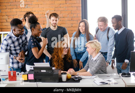 Group of cheerful businesspeople congratulating their red-haired co-worker with career development - Stock Photo