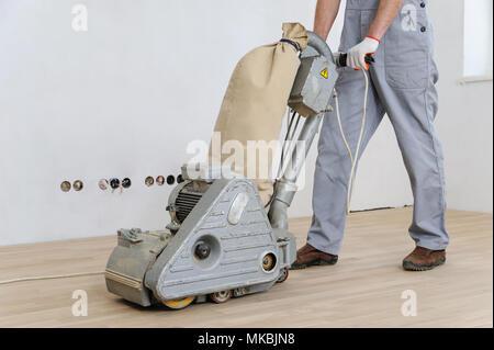 Worker polishing hardwood parquet floor with grinding machine. - Stock Photo
