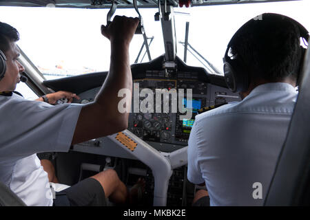 View of the cockpit of a small airplane flying in the sky. Team of pilots on plane, crew touching equipment and commands on dashboard - Stock Photo