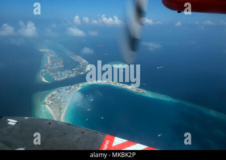 Aerial view of atolls, islands in Maldives, Asia, Indian Ocean. Archipelago, resort in tropical paradise seen from sky on airplane, plane, seaplane, f - Stock Photo
