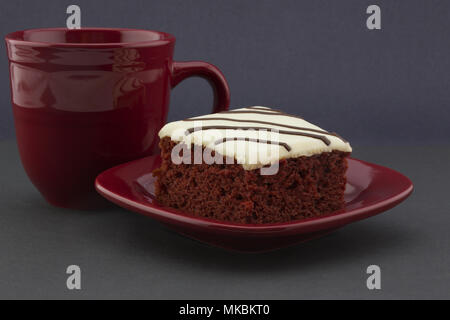 Three reds seens in red velvet cake, crimson mug, and matching plate against black background offer casual, holiday appeal. - Stock Photo