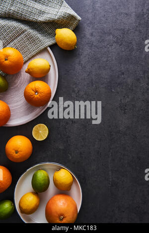 Top view of fresh ripe citruses. Lemons, limes, oranges and grapefruits on dark concrete background. Flat lay with copy space. - Stock Photo