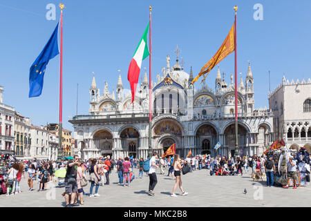 Basilica San Marco (St Marks Cathedral) in Piazza San Marco, (St Marks Square) with the flags of Venice, EU and Italy flying on Liberation Day, Venice - Stock Photo