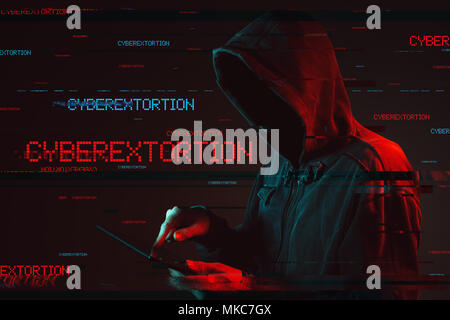 Cyberextortion concept with faceless hooded male person using tablet computer, low key red and blue lit image and digital glitch effect - Stock Photo