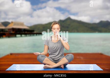 woman making yoga in and meditating lotus pose - Stock Photo