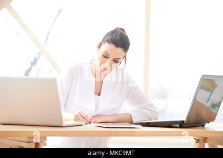 Portrait of smiling young sales assistant woman doing some paperwork while sitting at office desk in front of laptop and working online. Home office. - Stock Photo