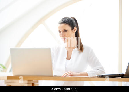 Portrait of attractive young sales assistant businesswoman using laptop at the office. - Stock Photo