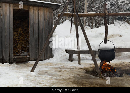 Cast iron cauldron of maple sap cooking over an open flame at the Annual Sugar Bush event at King's Landing Historical Settlement, New Brunswick, CA. - Stock Photo