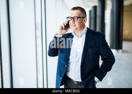 Positive confident successful businessman in formal suit standing at window and contemplating cityscape while talking on mobile phone on office - Stock Photo