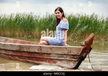 Pretty woman in an Old Wooden fishing boat. Beautiful woman smiling while sitting in a boat - Stock Photo