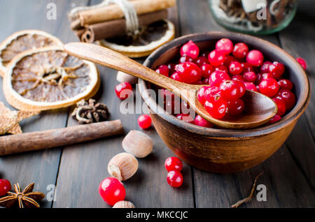 juicy raw cranberries in a ceramic plate, cinnamon stick, anise and dry orange on a dark old wooden table, ingridients for winter drink , copy space - Stock Photo