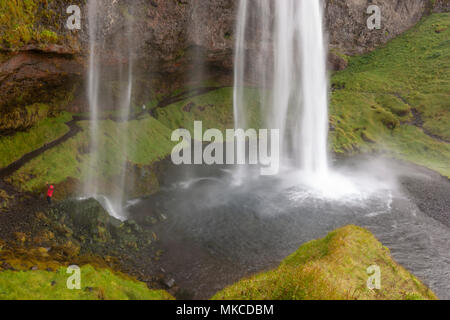Tourist in front Seljalandsfoss waterfall cave, Iceland - Stock Photo
