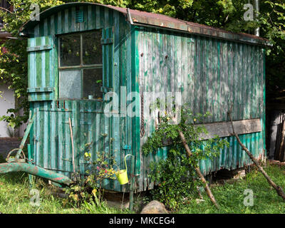 Old weathered wooden contractor's shed in the garden - Stock Photo
