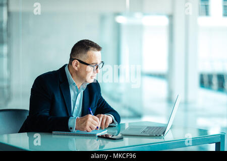 Shot of a senior financial businessman sitting at his workstation in front of computer and laptop while doing some paperwork. - Stock Photo