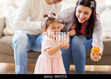 baby girl with parents at home birthday party - Stock Photo