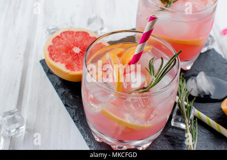 Cocktail with grapefruit slices and ice, ingredients for a drink on white wooden table, copy space - Stock Photo