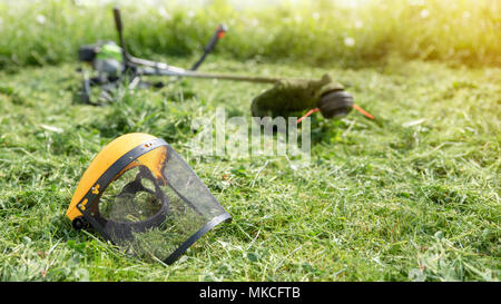 String trimmer and protective face mask on mown grass, growing grass on the background, banner 16x9 format - Stock Photo