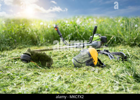 String trimmer and protective face mask on mown grass, growing grass and the blue sky on the background, sunlight - Stock Photo