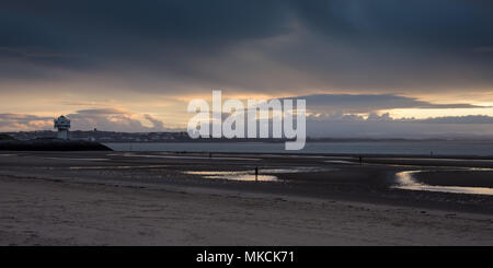 Liverpool, England, UK - November 12, 2016: The sun sets behind Antony Gormley's 'Another Place' sculptures on Crosby Beach, with the mountains of Sno - Stock Photo