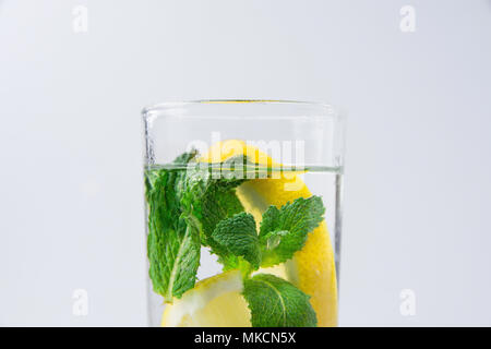 Fresh Cool Infused Detox Water with Ripe Organic Sliced Lemons Mint in Tall Glass. White Background. Healthy Drink Detox Summer Refreshment. Copy Spac - Stock Photo