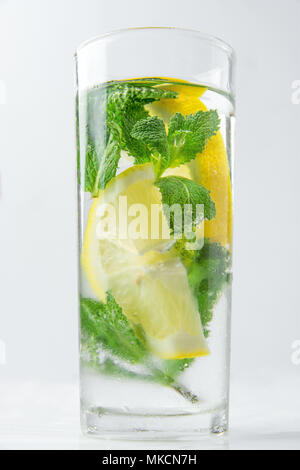 Fresh Cool Infused Detox Water with Ripe Organic Sliced Lemons Mint in Tall Frosty Glass. White Background. Healthy Drink Detox Summer Refreshment. Co - Stock Photo