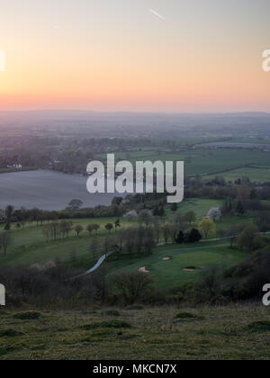 The sun sets over fields and villages in the agricultural landscape of the Aylesbury Vale, viewed from Combe Hill on the scarp of the Chiltern Hills. - Stock Photo