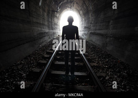 Man silhouetted in a tunnel standing in the center of the railway tracks looking towards the light at the end of the tunnel in a conceptual image - Stock Photo