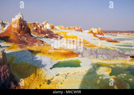 Yellow sulfuric volcanoes emitting toxic gas clouds, sulfur deposits white and green colors Danakil desert, north of Ethiopia. - Stock Photo