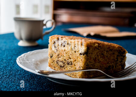 Carrot Cake with walnuts and cinnamon on blue surface. - Stock Photo
