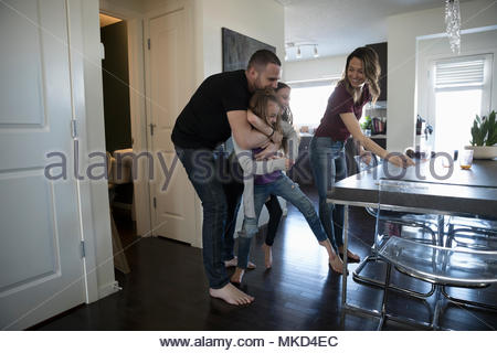Playful father hugging daughters in dining room - Stock Photo