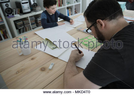 Father and son drawing at dining table - Stock Photo