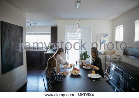 Mother and daughters eating waffles at breakfast dining table - Stock Photo