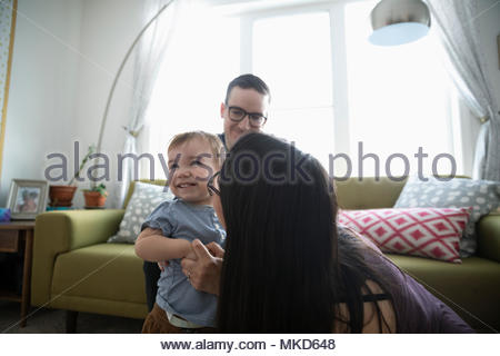 Affectionate parents playing with happy baby son in living room - Stock Photo