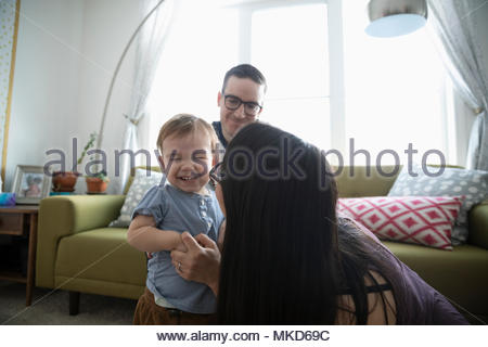 Affectionate parents playing with laughing baby son in living room - Stock Photo