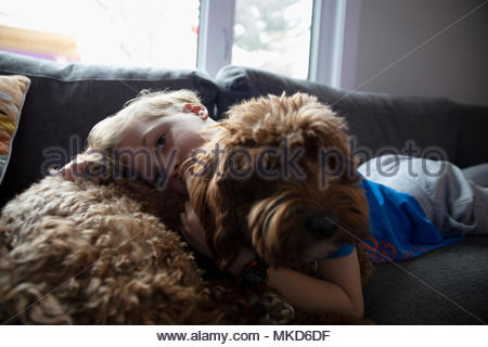 Portrait affectionate boy cuddling cute dog on living room sofa - Stock Photo