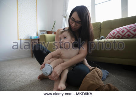 Mother dressing, putting socks on baby son - Stock Photo