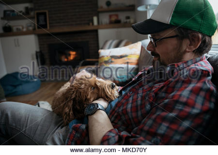 Man petting cute dog on living room sofa - Stock Photo
