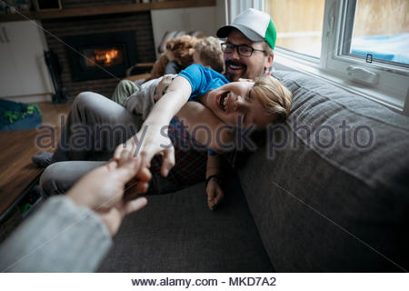 Personal perspective family playing on living room sofa - Stock Photo