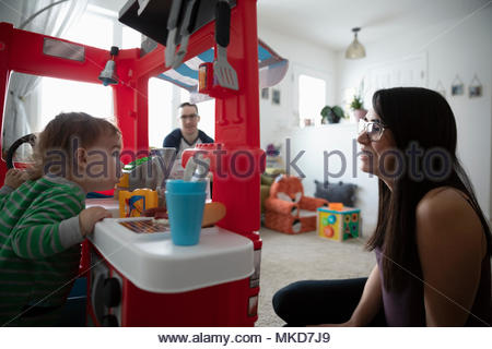 Parents watching baby son playing in toy kitchen - Stock Photo