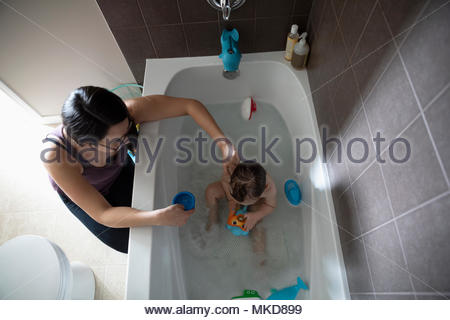 Mother bathing baby son taking bath, playing with toys in bathtub - Stock Photo