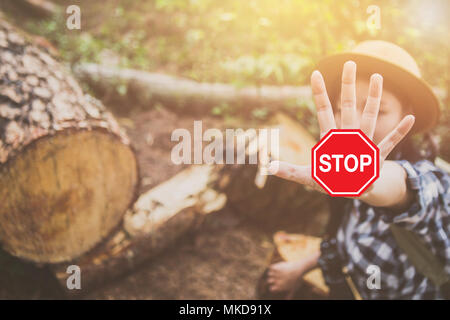 Deforestation,A young woman lifts a stop sign. - Stock Photo