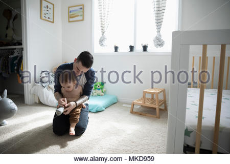 Father dressing, putting socks on baby son in nursery - Stock Photo