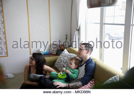 Young family eating, watching TV on living room sofa - Stock Photo