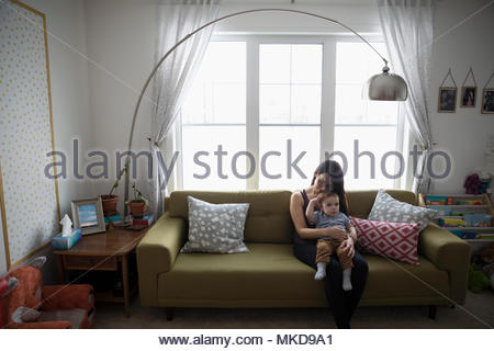 Affectionate mother holding baby son on living room sofa - Stock Photo