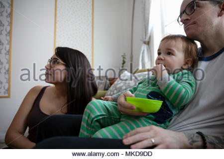 Young family eating, watching TV - Stock Photo