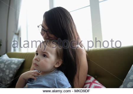 Affectionate, tender mother holding baby son on sofa - Stock Photo