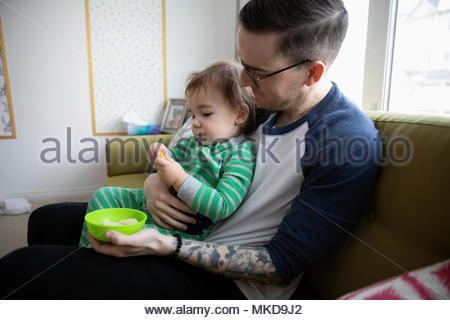 Father feeding baby son on sofa - Stock Photo