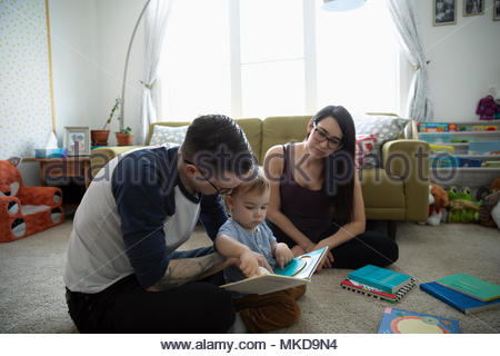 Parents reading story book to baby son in living room - Stock Photo