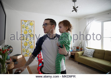 Father holding baby son, watching TV in living room - Stock Photo